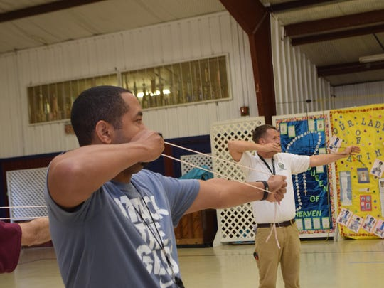 Jarome Davis (left), physical education teacher at Horseshoe Elementary School, was one of about 20 P.E. teachers learning the fundamentals of archery Thursday at St. Frances Cabrini Elementary School from Robert Stroede, state coordinator with Archery in Louisiana Schools. Training was provided through ALAS with the Louisiana Department of Wildlife and Fisheries. The coaches can then teach the sport to their students.