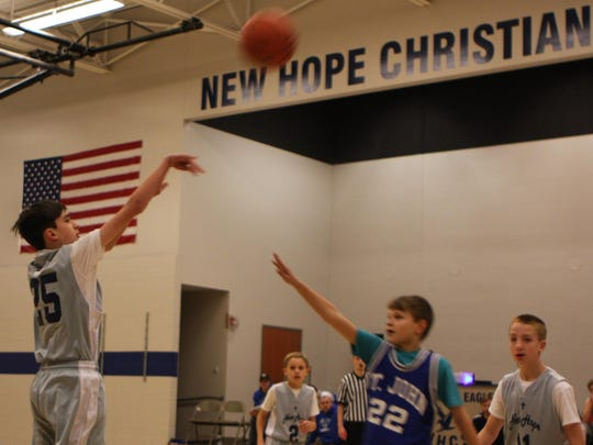 Trevor Ahonen, from left, Luke Slaats, Ethan Pomerenke and Coach Chad Urban during a basketball game at New Hope Christian School.