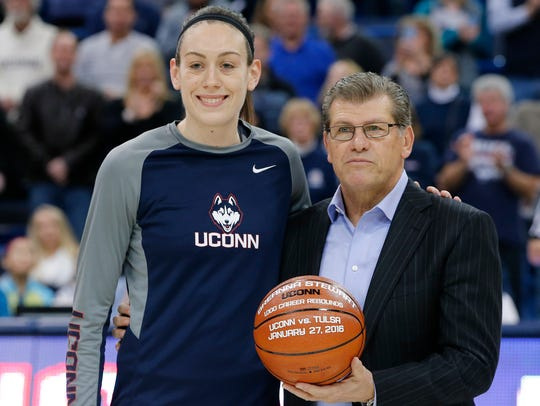 Connecticut coach Geno Auriemma poses with one of his