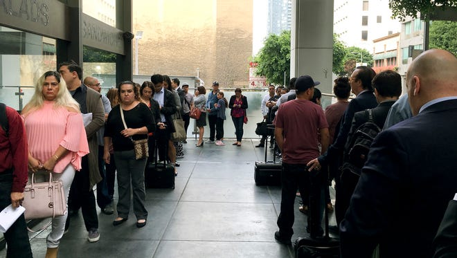 Immigrants awaiting deportation hearings, line up outside the building that houses the immigration courts in Los Angeles. Inside the courtroom, immigrant children who arrived on the U.S. border seeking asylum or other relief attended a special hearing for juveniles on the status of their cases.