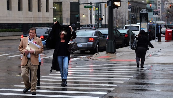 A woman covers her head against the rain and wind as she crosses Washington at Fort in downtown Detroit Thursday morning.