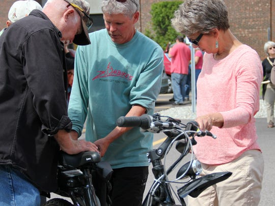 Larry Gilbert, center, shows an electric-powered Zoombike to Jim and Miriam Henrikson of Milton at the SUN CARnival, hosted by SunCommon, at St. Michael's College on Sunday.