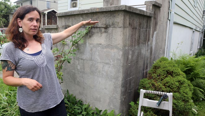 Jessica Kesselman of Piermont indicates how high water rose against the house she rents with her husband Rich Bertoli during Hurricane Sandy. They were covered by renter's insurance.