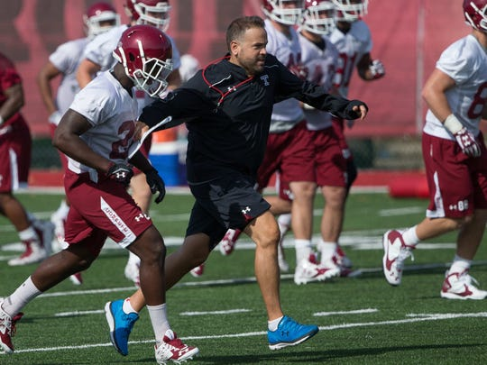 Hhead coach Matt Rhule runs up the field with his team