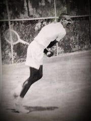 Tom Robinson is shown following through on a serve during a match in the late 1950s.