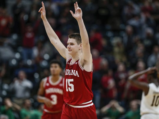 Notre Dame Fighting Irish guard TJ Gibbs (10) holds his hands on his head in disbelief as Indiana Hoosiers guard Zach McRoberts (15) watks off the court after the Hoosiers' 80-77 victory in overtime during the Crossroads Classic at Bankers Life Fieldhouse in Indianapolis on Saturday, Dec. 16, 2017.