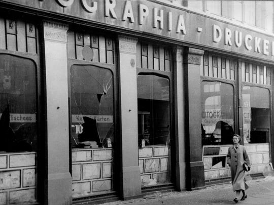 A woman walks past broken windows of Jewish-owned shops in Berlin on Nov. 10, 1938.  The Nazis attacked Jewish businesses on what was called the Night of Broken Glass,  which some historians consider the beginning of the Holocaust.