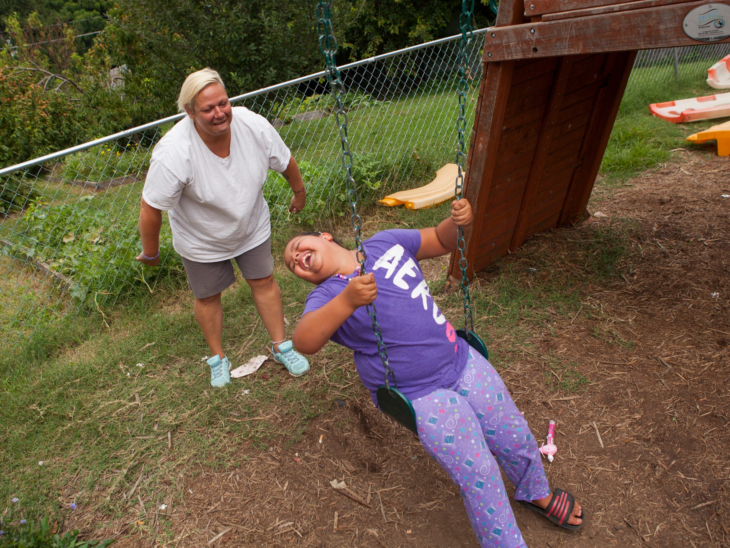 Constance Nettles pushes her daughter, Olivia Nettles, 7, on a swing outside The Valley Mission on Aug. 8, 2015. Constance is unable to work because of a physical disability and the family has been living on one income.
