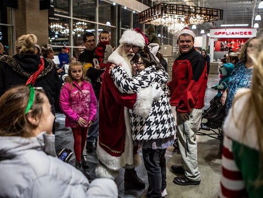 People rushed to give Santa a hug as he walked through