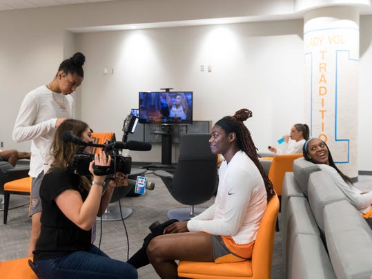 Tennessee's Cheridene Green gets interviewed while surrounded by teammates, Evina Westbrook, left, and Kasiyahna Kushkituah, right, inside the Tennessee locker room in Knoxville, Tenn., on Thursday, March 15, 2018. Tennessee will host Liberty in the first round of the NCAA women's basketball tournament. (Saul Young/Knoxville News Sentinel via AP)