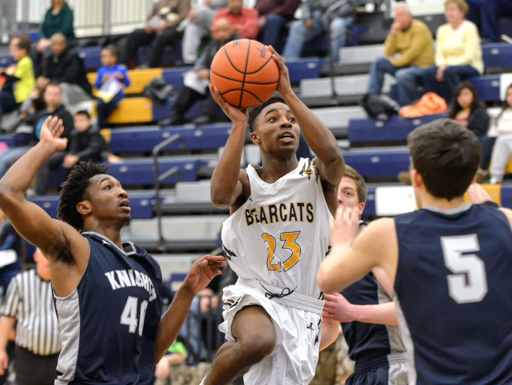 Central's Dontell Hardy (23) drives for the basket between Loy Norrix defenders.