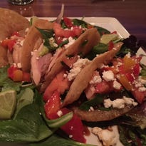 Smoked trout tacos feature soy, wasabi, field greens, peppers, tomatoes, feta and a squeeze of lime.