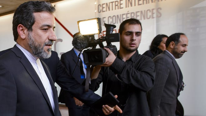 Iranian Deputy Foreign Minister Abbas Araghchi, left, leaves the media center after the start of two days of closed-door nuclear talks Oct. 15 at the United Nations offices in Geneva.