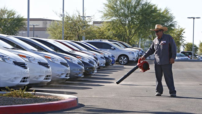 Jesus Lopez cleans the car lot at Coulter Nissan at the Surprise Auto Mall in Surprise on August 27, 2015.