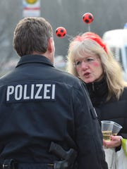 A woman dressed up for carnival talks to a policeman