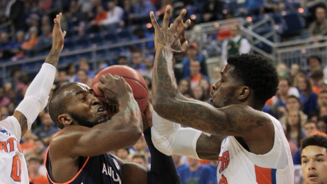 Auburn Tigers guard KT Harrell (1) tries to shoot between Florida Gators guard Kasey Hill (0) and forward Chris Walker (23) during the first half of an NCAA basketball game at Stephen C. O'Connell Center.