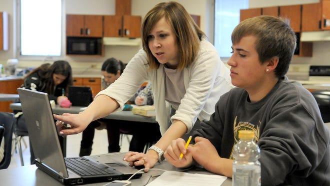 Pulaski teacher Liz Moehr works with a student in 2013.
