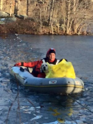 Emergency personnel rescue a dog and teenager who were stranded on a small island in a pond located near Camp Discovery in Croton-On-Hudson on Saturday, Feb. 20, 2016.