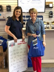 Kaptel customer service rep Kim Potier poses with local teacher Stacy Broussard at Kaptel's Abbeville store.
