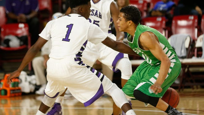 St. Mary's Marcus Shaver dribbles the ball behind his back while defended by Cesar Chavez's Tarion May (1) during the MLK Basketball Classic at Wells Fargo Arena on Jan. 19, 2015.