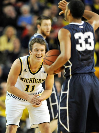 Michigan guard Andrew Dakich (11) applauds after Michigan