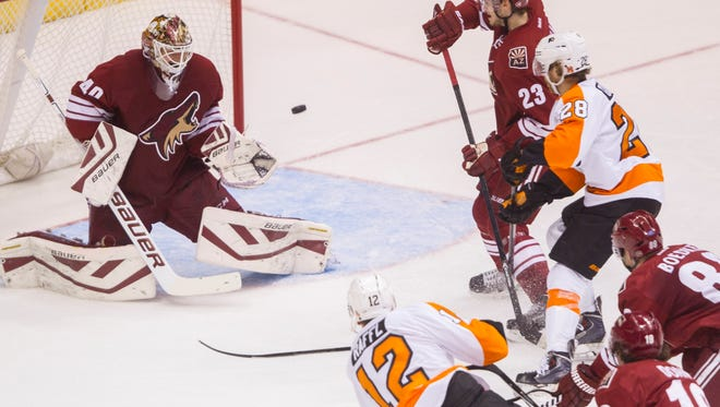 Coyotes' Devan Dubnyk (40) makes a save against a shot from Flyers' Michael Raffl (12) in the second period at Gila River Arena in Glendale on Dec. 29, 2014.