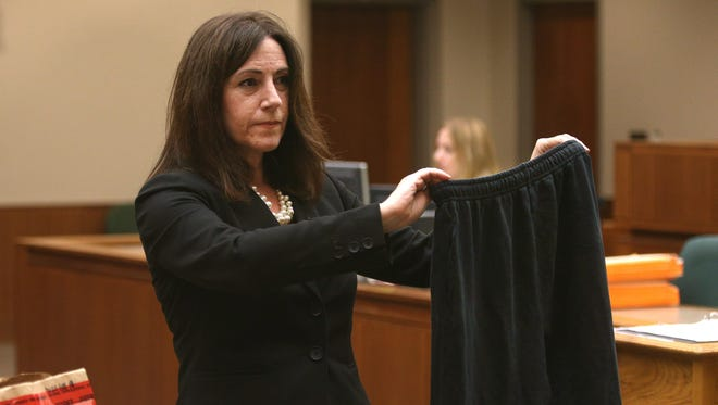 Julie Cianca, attorney for Alexander Rideout, holds up a pair of sweatpants that were introduced as evidence in the slaying of Craig Rideout, during her closing statements to the jury.