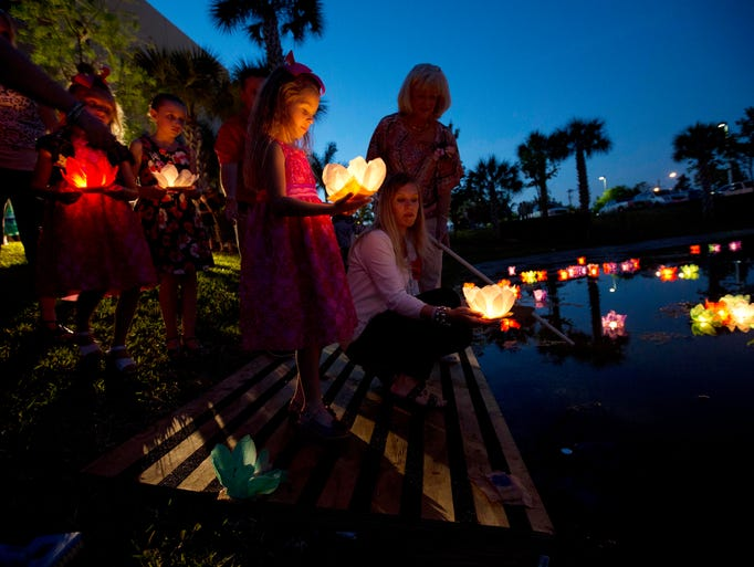 Haley McKinnon and her mother Julia send a lighted candle into a pond in front of the Cape Coral Police Department in honor of Payton McKinnon, 17 mos, who died after being left unattended in a vehicle in 2010.  They were attending a an annual vigil for families who've lost loved ones to all different types circumstances which inlude, violent crimes, natural death and or suicide.   On the upper right is Cape Coral victim's advocate Patricia Lucas.