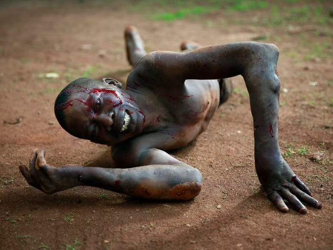 Kevin, a man accused of being a thief by civil servants at the Work Inspection office, lies in pain after being attacked by a man with a machete and sticks in plain view of others in Bangui, Central African Republic on Friday, April 18, 2014.