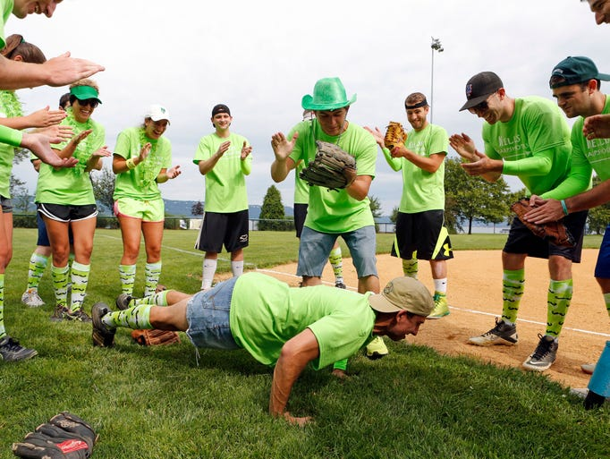 Ryan Mee, 23, standing at center, and a tournament organizer John Tessitore, 24, pump up the Kelly's Sharpshooters before playing the 4th annual JCK Legends softball tournament in honor of John Kelly, who died at age 24 after a long battle with Obsessive Compulsive Disorder, July 26, 2014 at Scenic Hudson Park in Irvington. Friends of John Kelly helped create the tournament and the JCK Foundation to raise awareness about Obsessive Compulsive Disorder and other mental disorders. All proceeds will benefit the foundation and their mission in educating the public. The foundation's website is www.jckfoundation.org