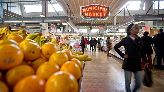 FILE - This Dec. 20, 2013, file photo shows shoppers passing through the Sweet Auburn Curb Market in Atlanta. Cuts to the nation's food stamp program enacted earlier this year are only affecting four states, far from the sweeping reform that Republicans had pushed, according to an Associated Press review. As a result, it's unclear if the law will realize the estimated $8.6 billion in savings over 10 years that the GOP had touted.  (AP Photo/David Goldman, File)