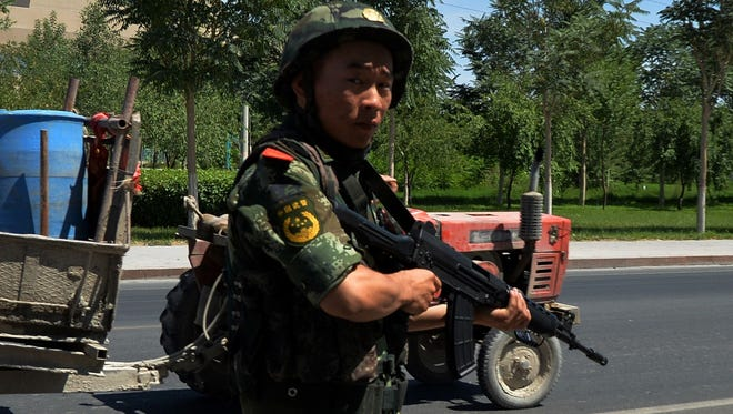 Chinese paramilitary police man a checkpoint on the road to the riot-affected Uighur town of Lukqun, Xinjiang province.