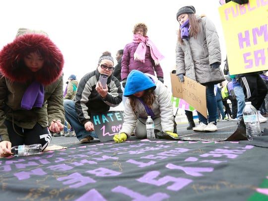 """Participants sign a petition of a Hmong quilt during a youth-led rally """"A Hate Crime Is A Crime"""" Saturday, March 18, 2017, at the Goerke Field in Stevens Point, Wisconsin."""