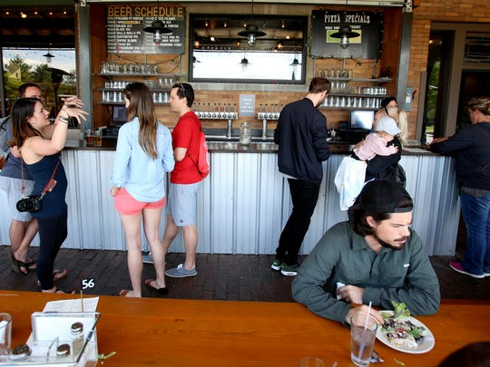 People talk, eat and drink at The Filling Station Microbrewery