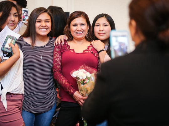 Alma Perez takes a photo of Maria Julia Ramos, center, with family at the end of the naturalization ceremony Wednesday, Sept. 6, 2017, at O.C. Fisher Federal Building.
