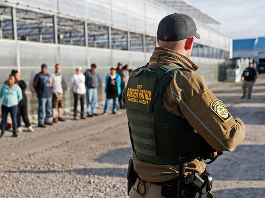 In this June 5, file photo, government agents stand watch over suspects taken into custody during an immigration sting at Corso's Flower and Garden Center in Castalia.