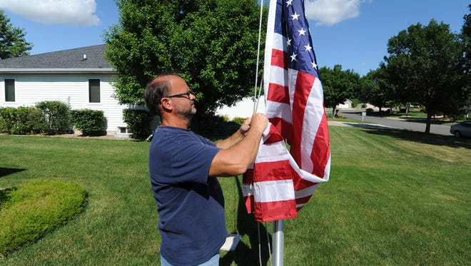 George Rapp of Fly-Me-Flag installs a 20-foot flagpole in a De Pere yard Thursday.