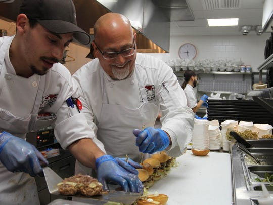 Anthony Casciotta gets some help from Executive Chef David Maini, on right, during a preview for the grand opening of Zinburger Wine & Burger Bar in Morris Plains.