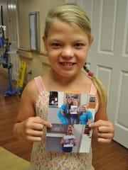 Addisyn James holds the new pictures of herself that now hang in the Rapides Regional Medical Center NICU. The top one shows James with the nurses who cared for her in 2010. The bottom one shows her holding the picture of herself leaving the helicopter.