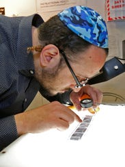 Lipa Schmeltzer looks over some of his negatives in
