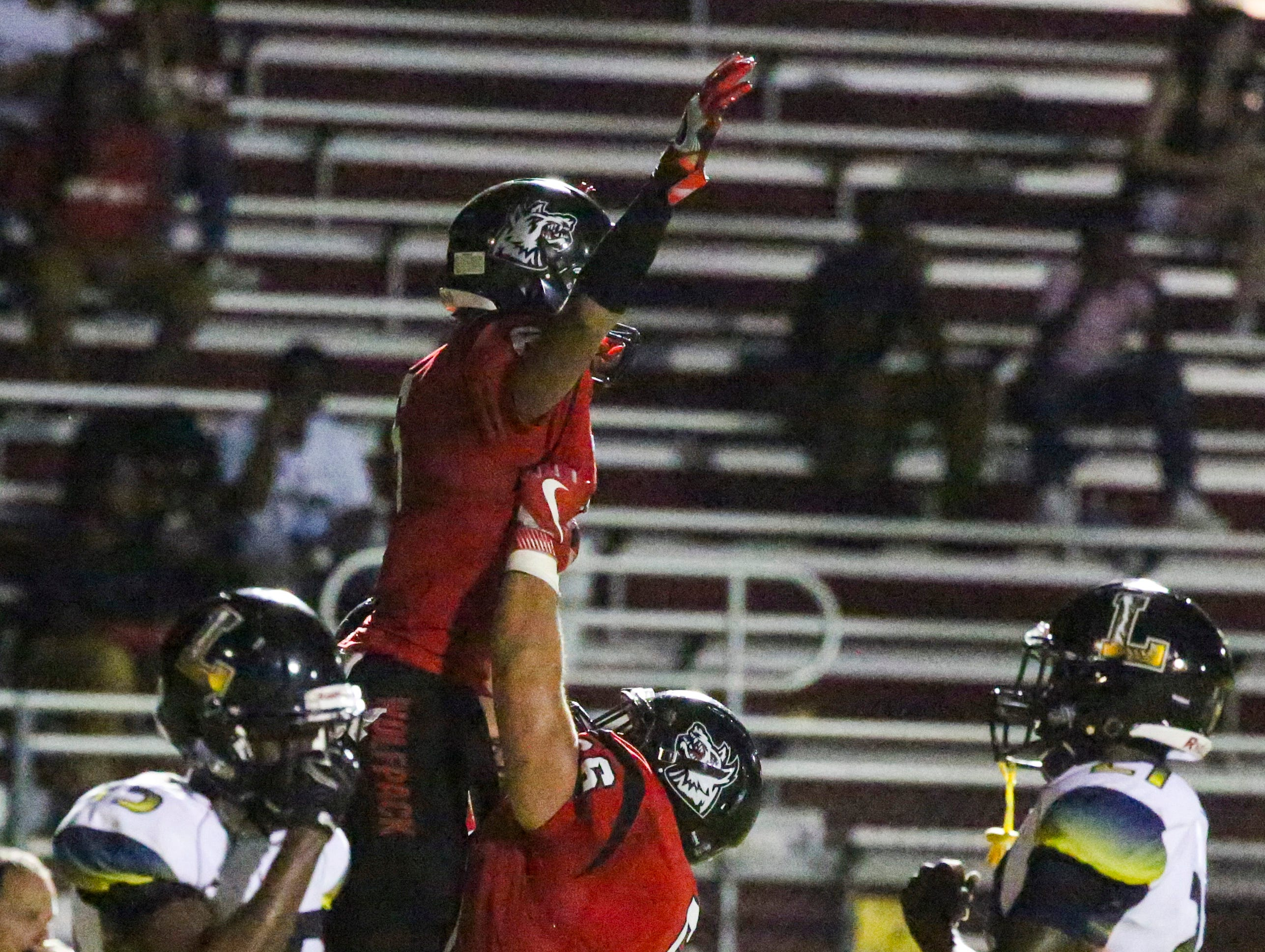 Bobby Souza lifts up teammate Jeshuan Jones in celebration after Jones scored in their third quarter for South Fort Myers. Lehigh played South Fort Myers in their football Friday night.