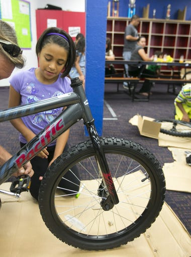 Volunteer, Bruce Moses and Zayda Mendoza, 9, of Phoenix  work on building her bike at the Build-A-Bike event at the I.G. Homes Branch of the Boys & Girls Clubs of Metro Phoenix.