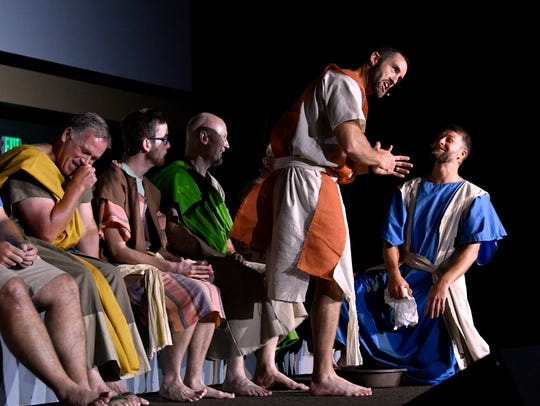 "Mark Rogers stands while Dillon Cobb, who plays Jesus, kneels during a foot-washing scene during rehearsal Wednesday at Southern Hills Church of Christ for ""Jesus: Life of Love."""