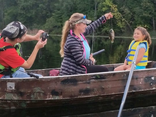 While her mom, Liz, captured the action on camera, 4-year-old Ainsley Melotte got some help from Tammy Naze after catching a bluegill on West Alaska Lake.