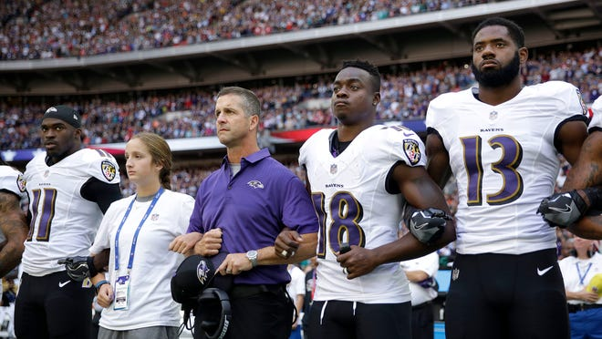 Baltimore Ravens head coach John Harbaugh, center left, links arms with his daughter Alison and wide receiver Jeremy Maclin (18) during the playing of the U.S. national anthem before an NFL football game against the Jacksonville Jaguars at Wembley Stadium in London, Sunday Sept. 24, 2017. Also pictured are Breshad Perriman (11) and Chris Matthews (13). (AP Photo/Matt Dunham)