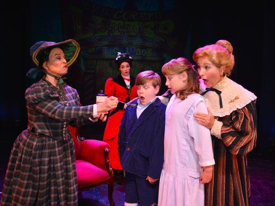 The mean nanny Miss Andrew (Mary Jo Marzilli-Mendola) offers castor oil to Michael and Jane Banks (Zachary Grandey and Karly Dribble) as Jane Banks (Brenda Sheets) looks during Cocoa Village Playhouse's April showing Mary Poppins.