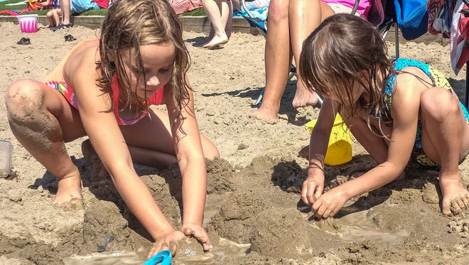 Avery Daniels, 8, left, and Grace Cleland, 4, make sand castles at Hawk Island Sunday, September 4, 2016. The Ingham County Parks water features will close after Labor Day.