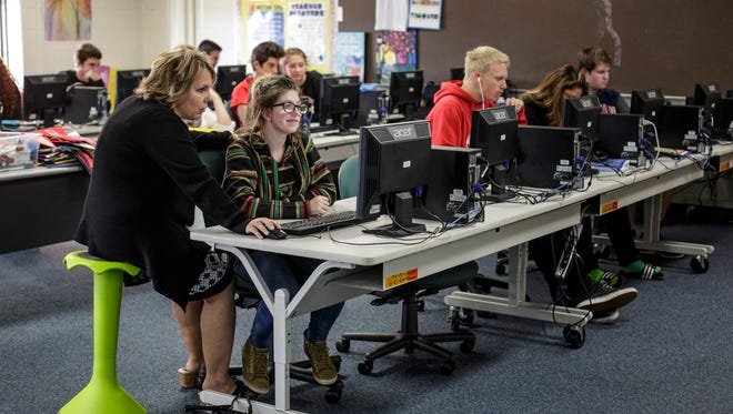 Laurie Gardner helps Lillian Shay, 16, during a business essentials class Wednesday, Oct. 19, 2016 at Marine City High School. Laurie Gardner is redesigning her classroom as part of the St. Clair County RESA Classrooms 4 the Future program. The green chair, which pivots on a ball, is a piece of furniture being tested before the redesign.