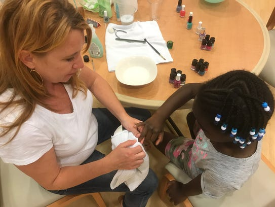 Laura Baird gives a manicure to one of the young ladies