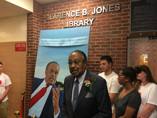 Clarence B. Jones stands in front of a portrait of